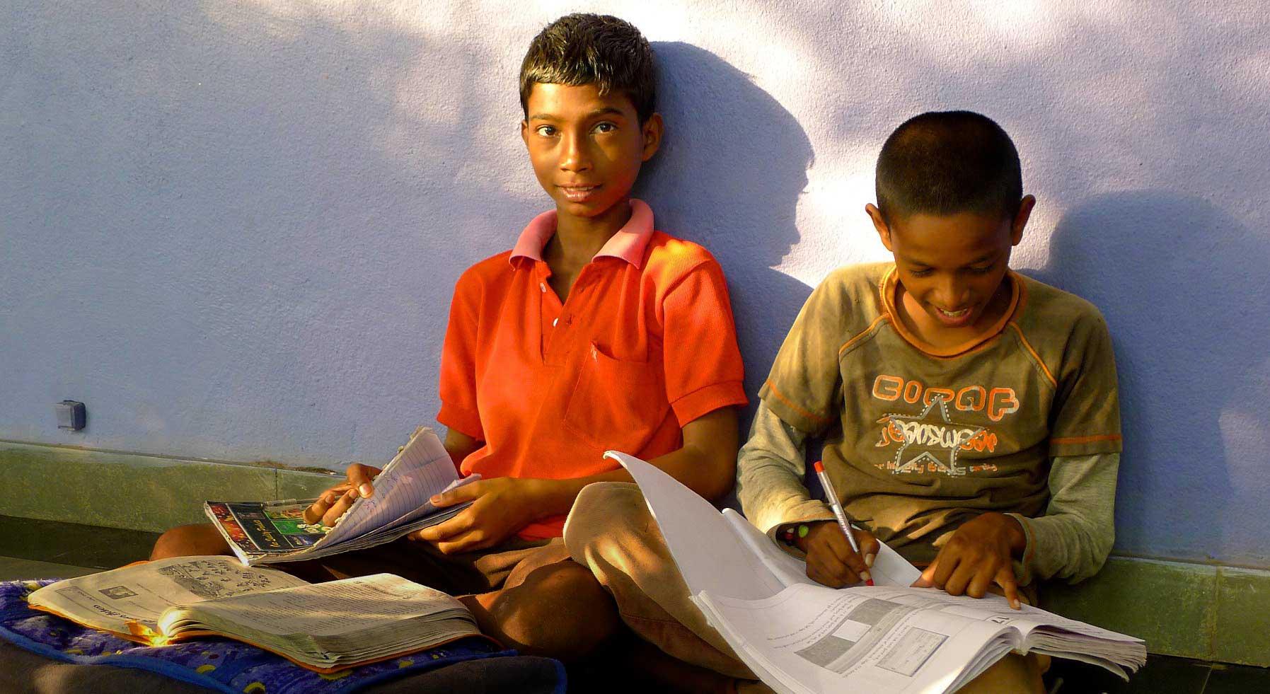 deux garçons souriants en train de faire leurs devoirs d'école
